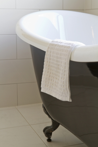 Close up of a black clawfoot bath in a contemporary bathroom