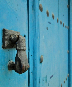 Blue wooden door with iron hand door knocker in Spain.